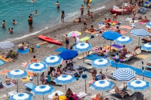 AMALFI, ITALY - JUNE 28, 2014: People enjoy a beach at picturesque summer landscape of town Amalfi, Italy. Amalfi is included in theUNESCO World Heritage Sites.